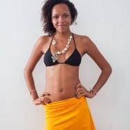 Joy in a black bikini and yellow skirt